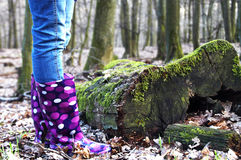 Female rain boots. Female legs closeup wearing rain boots in nature royalty free stock images