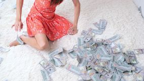 Female raking lot of banknotes of dollars on the bed, lot of money, slow motion, top view.  stock video