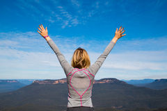 Female reaching for the sky. Sporty woman reaching for the sky on a mountain top stock images