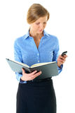 Female read notes in her diary and check mobile Royalty Free Stock Image