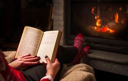 Female reading a book by the fireplace. Cozy winter lifestyle Stock Image