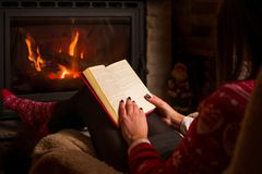 Female reading a book by the fireplace. Cozy winter lifestyle Stock Photography