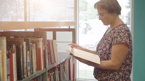 Woman reading book in library stock video footage