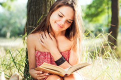 Female reading book in park. Young beautiful caucasian female reading book in park Stock Images