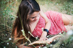 Female reading book in park. Young beautiful caucasian female reading book in park Royalty Free Stock Images