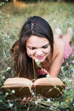 Female reading book in park. Young beautiful caucasian female reading book in park Stock Photos