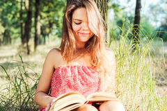 Female reading book in park. Young beautiful caucasian female reading book in park Royalty Free Stock Photos