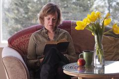 Female reading book by table with daffodils Royalty Free Stock Images