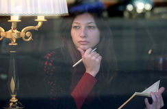 Female reading a book and thinking. View through the window Stock Photography