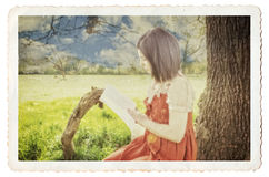 Female reading a book beside a tree. Female reading book under tree, vintage photograph look. Textured, gritty detail with soft focus, cracks and borders Stock Image