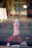 Female reading a book, view through the window Royalty Free Stock Photo