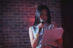 Female reading paper while performing in nightclub. Confident female reading paper while performing in nightclub Stock Image