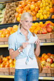 Female reads shopping list near the stack of fruits Stock Photo