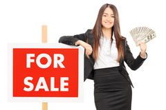 Female real estate agent holding money by a for sale sign Royalty Free Stock Images