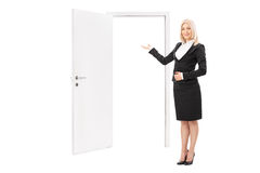 Female real estate agent pointing towards a door Royalty Free Stock Image