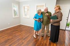 Female Real Estate Agent Handing New House Keys to Senior Adult royalty free stock image