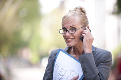 Female Real Estate Agent talking on phone Royalty Free Stock Images