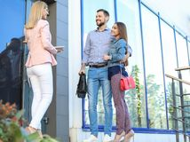 Female real estate agent welcoming couple to show house. Outdoors stock photos