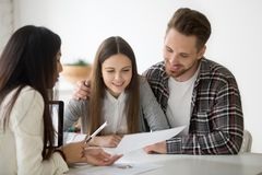 Female realtor consulting millennial spouse on property buying. Female realtor showing house plan to excited millennial couple buying first property together royalty free stock photo