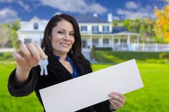 Female Realtor Holding Blank Sign and Keys In Front of House Royalty Free Stock Images