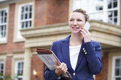Female Realtor On Phone Outside Residential Property Stock Images