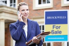 Female Realtor On Phone Outside Residential Property For Sale stock photo
