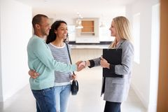 Free Female Realtor Shaking Hands With Couple Interested In Buying House Stock Photography - 157263432
