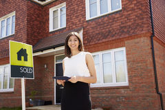 Female Realtor Standing Outside Residential Property stock images