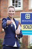 Female Realtor Standing Outside Residential Property Holding Key royalty free stock photo