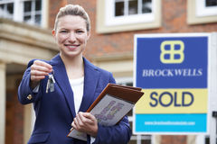 Female Realtor Standing Outside Residential Property Holding Key Royalty Free Stock Photos