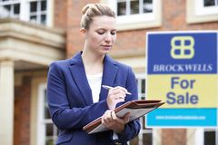 Female Realtor Standing Outside Residential Property With For Sa stock images