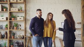 Female realtor in suit is showing loft style flat to young man and woman looking for new apartment. Buyers are excited. Female realtor in suit is showing loft stock video