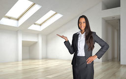Female Realty Agent Inside an Architectural Room. Close up Smiling Female Realty Agent in Business Suit Showing Inside of an Empty Architectural Room Stock Photos