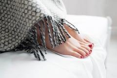 Female reams under warm gray blanket Stock Photo