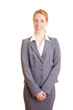 Female Receptionist. Blond happy businesswoman in a suit with isolated background royalty free stock image