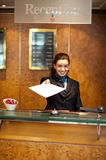 Female receptionist handing over check-out papers. Along with bill to the customer Royalty Free Stock Images