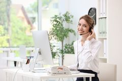 Female receptionist with headset. At desk in office stock photography