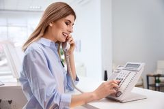 Female receptionist talking on phone at hotel check. In counter Royalty Free Stock Photography