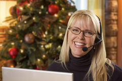 Female Receptionist Using Laptop Wearing Phone Headset Near Christmas Tree Royalty Free Stock Image