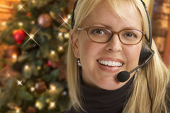 Female Receptionist Wearing Phone Headset In Front of Christmas Tree Stock Photography