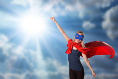 Female in red cape and blue mask on sky background, sunlight. Royalty Free Stock Photo