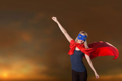 Female in red cape and blue mask on sky background, sunset. Stock Images