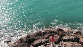 Female in red dress enjoying sun and warm wind standing on rocks on sea pier with arms apart. Aerial view of woman in red outfit o stock footage