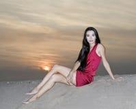 Female in red dress posing at the desert Stock Photo