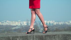 Female in red dress and in shoes on high heels walks at blurred city background. Beautiful legs of businesswoman in red dress. The woman in black shoes on heels stock video