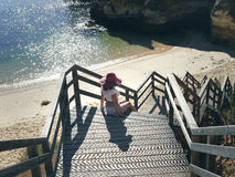 Female  in a red hat on the wooden steps of the stairs on the beach in Portugal Royalty Free Stock Photos