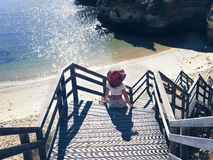 Female  in a red hat on the wooden steps of the stairs on the beach in Portugal Royalty Free Stock Images