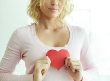 Female with red heart. Close-up of pretty female with red paper heart royalty free stock image