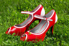 Female red high heel shoe on green grass Royalty Free Stock Image