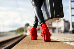 Female with red high heels and suitcase in train station Royalty Free Stock Photography